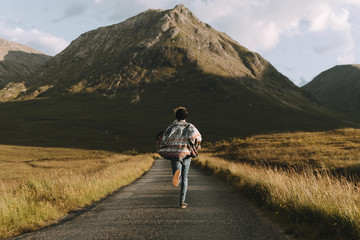 Adventurous Young adult male wearing jeans and a colorful flanel shirt running down a road towards a mountain at sunset
