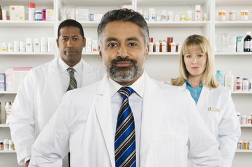 Portrait of a confident male pharmacist standing with two colleagues at pharmacy