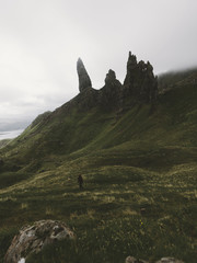 Young adult woman walking up the mountain in front of the old man of storr volcanic stone formation panorama with a dramatic and hazy sky