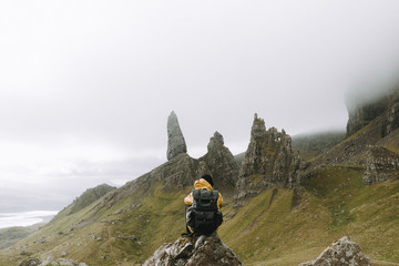Young adult man wearing a yellow coat and black backpack sitting in front of the old man of storr volcanic stone formation panorama with a dramatic and hazy sky