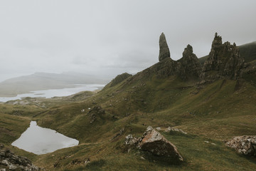 Panorama of the Old man of  Storr volcanic Stone formation with lake and green grass and dramatic sky in the distance