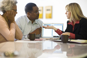 Financial advisor assisting an African American couple at home