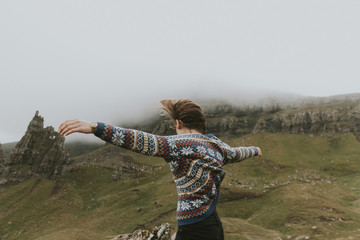 Young woman wearing a colorful sweater dancing in the wind in the mountains with flowing hair