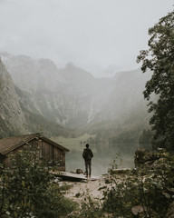 Young male standing by a foggy moody lake near a boat house and forest with mountains in the background