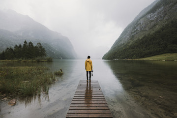 Young adult male wearing yellow jacket standing on a footbridge at a foggy mountain lake with forest