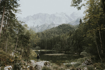 .Woman standing at a lake in the mountains surrounded by forest at daytime