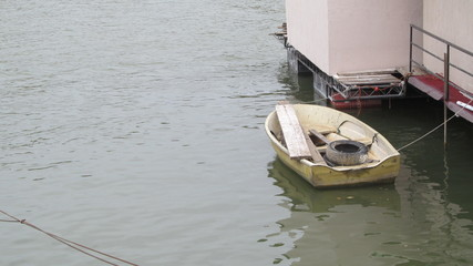 Ordinary small boat tied to float with old car tire as anchor