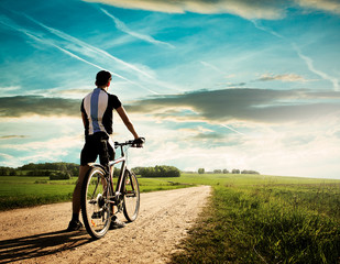 Rear View of a Young Man With Bicycle on Summer Nature Background. Healthy Lifestyle and Mountain Bike Cycling Concept. Toned Photo with Copy Space.
