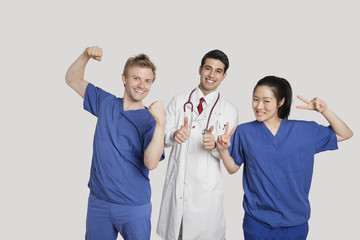 Portrait of a cheerful medical team gesturing over gray background