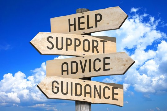 Wooden signpost with four arrows - help, support, advice, guidance - great for topics like frequently asked questions, customer support etc.