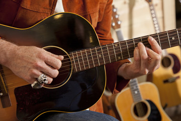 Close-up of man's torso practicing with guitar