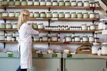 Senior female employee arranging spice jars on shelf