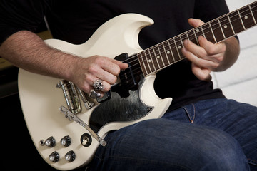 Close-up of mid adult man's torso playing guitar