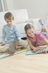 Siblings reading story books on floor in the living room