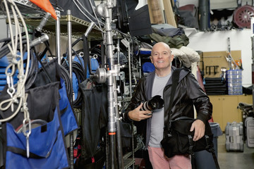 Portrait of a happy senior photographer in studio