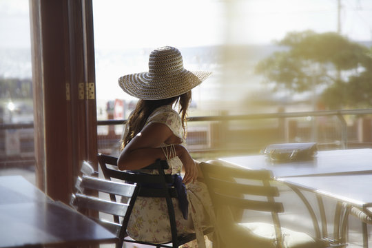 Rear view of young woman wearing sunhat at cafe