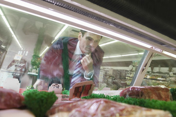 Mature man looks through glass of meat counter in supermarket