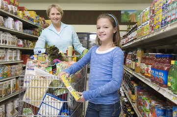 Smiling woman shopping with daughter in supermarket