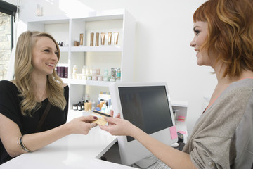 Happy young woman paying through credit card at hair salon