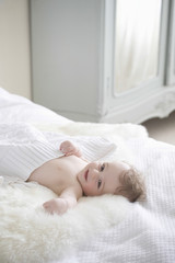 Portrait of happy adorable baby boy lying on fur blanket in bedroom