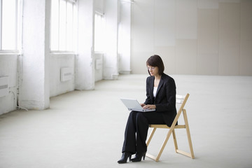 Full length of young businesswoman using laptop while sitting on chair in empty warehouse