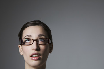 Young female wearing spectacles looking upwards isolated over grey background