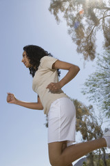 Low angle view of a female jogging against blue sky