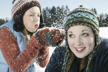 Playful teenage girl blowing snow on her friend in winter