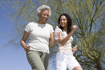 Happy African American mother and daughter jogging together