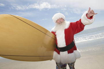 Cheerful man dressed in Santa Claus outfit holding surfboard standing on beach
