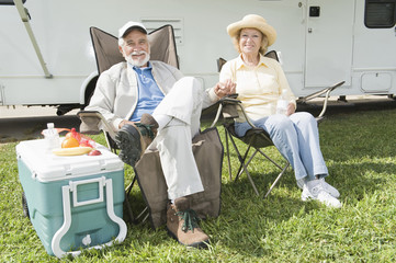 Full length of happy senior couple sitting on folding chairs outside RV home