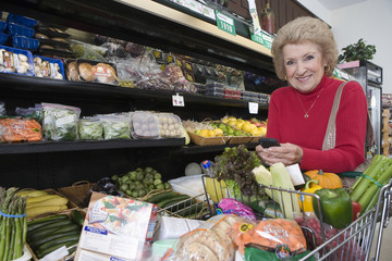 Portrait of smiling mature woman with cellphone while doing grocery shopping in supermarket