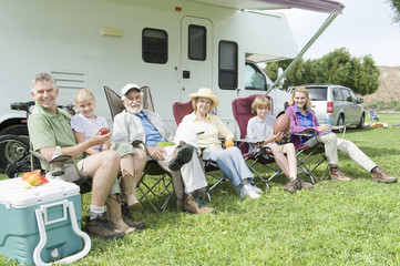 Portrait of happy three generational family sitting outside RV home