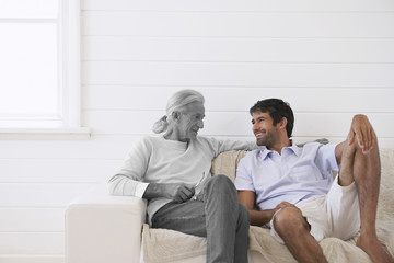 Senior man sitting on sofa at porch with mid adult son