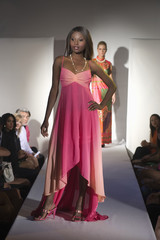 Beautiful African American woman in pink dress standing on ramp during a fashion show