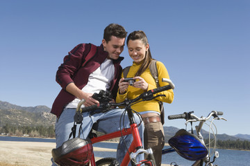 Young couple standing with mountain bikes looking at screen of camera