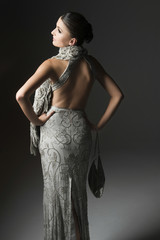Female fashion model posing in gray evening dress and scarf against gray background