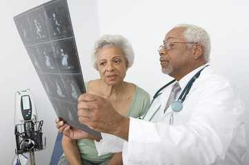 An African American male doctor explaining x-ray report to patient at clinic