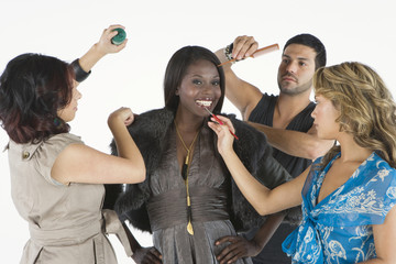 Three makeup artists assisting an African American fashion model isolated over white background