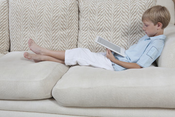 Side view of a relaxed little boy using digital tablet on sofa