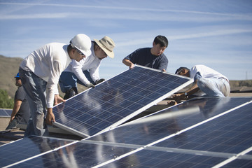 Group of multietchinc engineers placing solar panels on rooftop