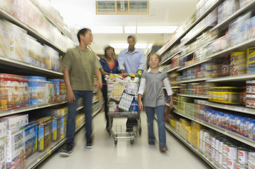 Full length of a family of four shopping in supermarket