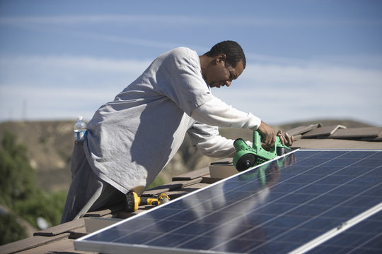 An African American man working on solar panelling on rooftop