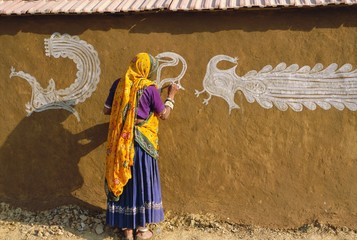 Woman decorating her house with traditional local designs, Tonk region, Rajasthan, India, Asia