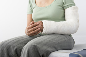 Midsection of a female with fractured hand sitting on bed at clinic