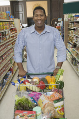 Portrait of a smiling man standing with grocery shopping in supermarket aisle