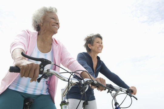 Low angle view of multiethnic senior female friends riding bicycles against sky