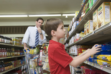 Thoughtful man shopping with son in supermarket