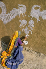 Woman painting designs on her house, Tonk region, Rajasthan state, India, Asia