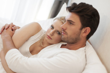 Loving young couple embracing in bed